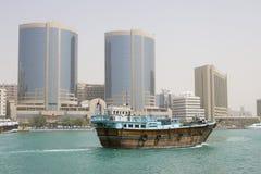 El velero de madera viejo del dhow de Dubai UAE A cruza abajo de Dubai Creek delante de la torre de Rolex. Imágenes de archivo libres de regalías