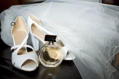 El velo de la novia con los zapatos y parfume en la butaca de cuero Fotos de archivo libres de regalías