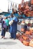 El vendedor africano vende los bolsos de cuero en el mercado de Sineu, Mallorca, España Imagenes de archivo