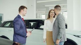El vendedor alegre de la concesión de coche está sacudiendo las manos con el hombre hermoso del comprador joven entonces que da e almacen de video
