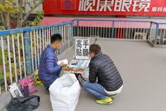 El vendedor ambulante masculino fijó la película protectora en el teléfono, adobe rgb Imagen de archivo libre de regalías