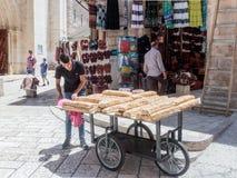 El vendedor ambulante vende los dulces cerca de la entrada al mercado de Suq Aftimos en la calle de Muristan en la ciudad vieja d imagen de archivo