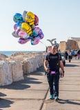 El vendedor ambulante vende los globos y los compradores el tentar en el agua Foto de archivo