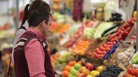 El vendedor ayuda al comprador a elegir las frutas y almacen de metraje de vídeo