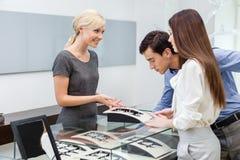 El vendedor ayuda a pares para seleccionar la joyería imagenes de archivo