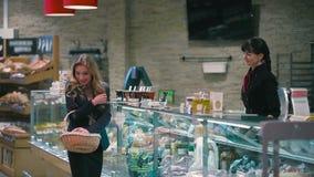 El vendedor da el tarro del escaparate al blonde joven metrajes