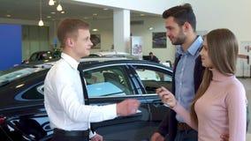 El vendedor da la llave del coche a los pares en la representación almacen de metraje de vídeo