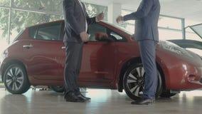 El vendedor da llaves del nuevo coche al cliente en concesión de coche metrajes