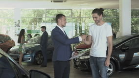 El vendedor da llaves un cliente feliz después de trato acertado del coche de compra almacen de video