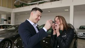 El vendedor de coches da a muchacha emocionada feliz joven las llaves a un nuevo coche almacen de video