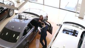 El vendedor de coches da a muchacha las llaves a su nuevo coche en la sala de exposición almacen de metraje de vídeo