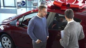 El vendedor de coches dice a comprador las características del coche almacen de metraje de vídeo