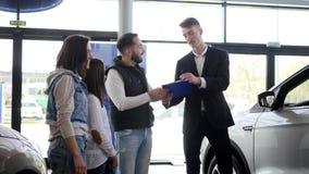 El vendedor de coches muestra una información joven de la familia sobre su nuevo coche metrajes