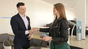 El vendedor de coches sacude las manos con una chica joven y da las llaves al nuevo coche metrajes