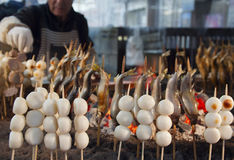 El vendedor de comida de la calle cocina las bolas de arroz yakitory y dulces en el fuego abierto Fotos de archivo libres de regalías