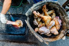 El vendedor de comida de la calle está asando a la parrilla las piernas del cerdo usando la lámpara de soldar fotos de archivo