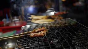 El vendedor de comida de la calle prepara y vende el cerdo en los palillos, Bbq de la parrilla frió la carne de cerdo en el merc almacen de metraje de vídeo