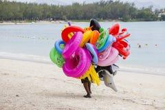 El vendedor de juguetes y de revestimientos inflables de la natación va a lo largo de la playa en la isla Mauricio Fotos de archivo libres de regalías