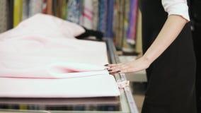 El vendedor de la muchacha con la manicura hermosa mide el paño en la tabla con centímetro y marca el pedazo correcto usando una  metrajes
