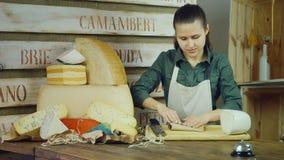 El vendedor de la mujer joven embala el queso, entonces sonriendo en la cámara metrajes
