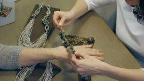 El vendedor de sexo femenino ayuda a la mujer elegante a intentar encendido una pulsera costosa