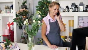 El vendedor del florista de la mujer en floristería toma orden en el teléfono y workes en el ordenador almacen de video