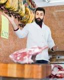El vendedor del hombre que agrupa la carne para vender en butcher's hace compras Foto de archivo libre de regalías