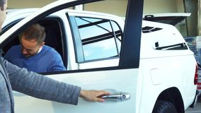 El vendedor elegante abre la puerta de coche e invita allí al comprador almacen de video