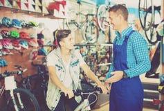 El vendedor en adolescente de ayuda uniforme elige la bicicleta Imagen de archivo libre de regalías