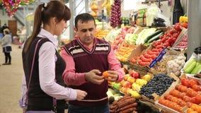 El vendedor en el mercado muestra la fruta del comprador y da a metrajes