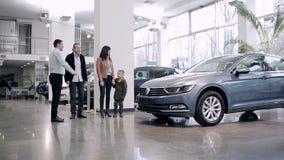 El vendedor encuentra a la familia en una sala de exposición del coche metrajes