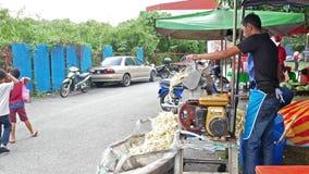 El vendedor está extrayendo el jugo fresco de la caña de azúcar cruda usando la máquina del jugo de la caña de azúcar