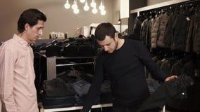 El vendedor está ofreciendo al comprador a intentar en los pantalones, encontrando tamaño conveniente metrajes
