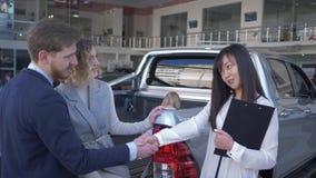 El vendedor feliz del coche aconseja a la familia de los compradores con la muchacha del niño en el tronco del vehículo y sacude  almacen de metraje de vídeo