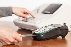 El vendedor hace el cálculo y toma el pago por un registro del efectivo Fotografía de archivo libre de regalías