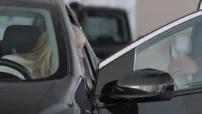 El vendedor invita a una mujer que examine el auto desde adentro almacen de metraje de vídeo