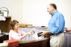 El vendedor lisiado sirve al cliente foto de archivo