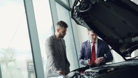 El vendedor profesional del automóvil está demostrando el motor de coche del cliente debajo de la capilla del motor, hombres está almacen de metraje de vídeo