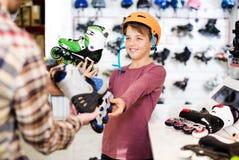 El vendedor que ayuda al muchacho en elegir patina sobre ruedas Imagen de archivo