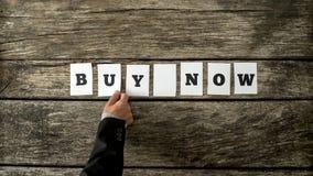 El vendedor que monta una compra ahora firma con la tarjeta blanca sobre un rústico Foto de archivo libre de regalías