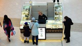 El vendedor sirve a los compradores de la bisutería en el contador de la exhibición almacen de video