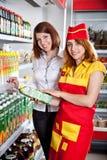 El vendedor y el comprador en departamento de tienda de comestibles Fotografía de archivo