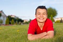 El verano adolescente de risa miente en la hierba Foto de archivo