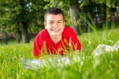El verano adolescente de risa miente en la hierba Imagen de archivo