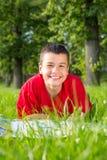 El verano adolescente de risa miente en la hierba Foto de archivo libre de regalías
