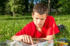 El verano adolescente serio miente en la hierba Fotos de archivo libres de regalías