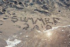 El verano 2018 de la palabra escrito en la arena en una playa Foto de archivo libre de regalías