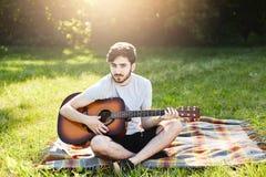 El verano que lleva del hombre barbudo hermoso viste sentarse en la sobrecama con la guitarra, disfrutando del tiempo soleado y l Fotografía de archivo