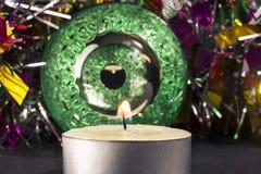 El verde grande talló la bola de Navidad del espejo con la vela y la malla, foco selectivo Foto de archivo libre de regalías