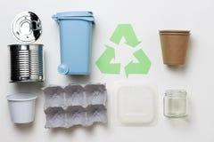 El verde recicla el s?mbolo y el pl?stico, basura de la basura del hierro en el fondo blanco, visi?n superior imagenes de archivo